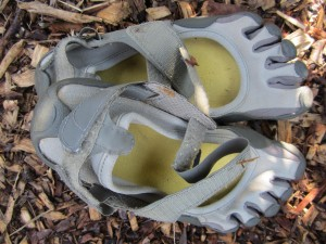 a pair of Vibrams lying on wood chips